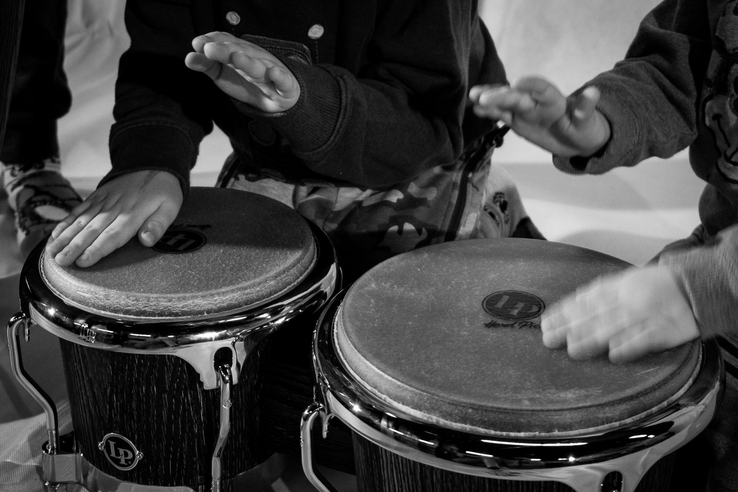 Children's hands drumming on congos.