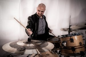 Man playing a Gretsch drum kit in a studio with a white backdrop.
