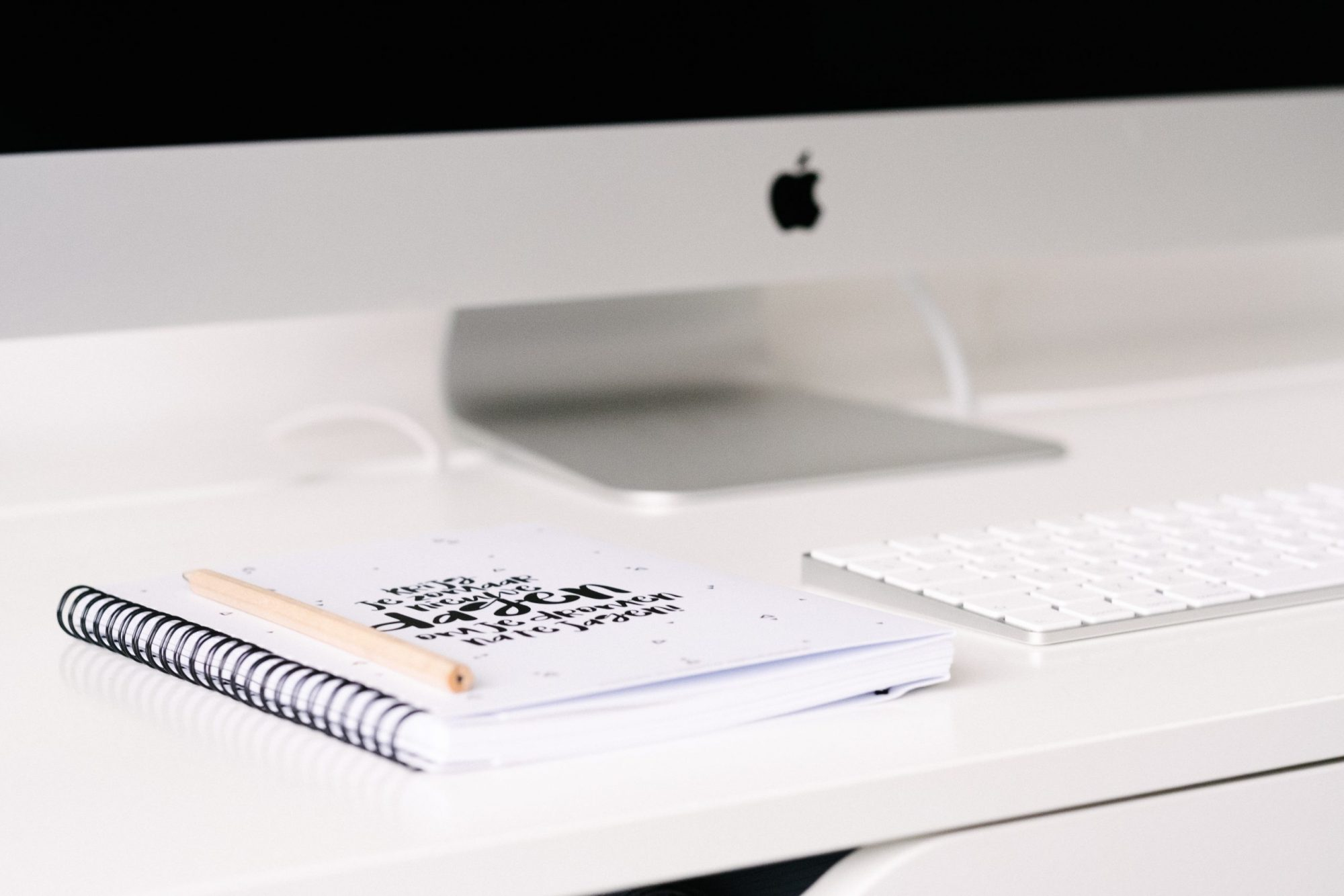 apple computer, keyboard and notebook on white desk
